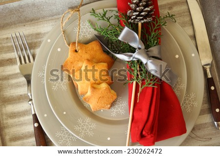 christmas table setting from above - elegant white plate with ginger cookies,  and natural pine tree branch on rustic planked wood. Country and retro style. - stock photo