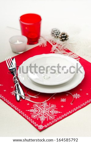 Christmas table setting in red and white with a red napkin and white embroidery with snowflakes - stock photo
