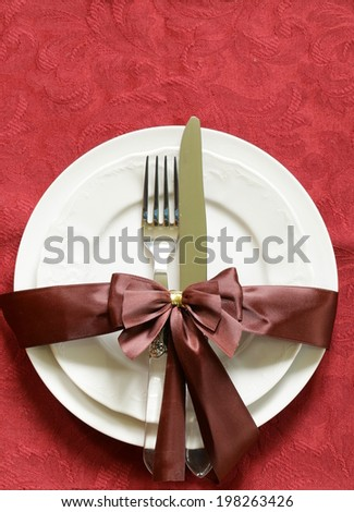 Christmas table setting (white plates on a red background) - stock photo