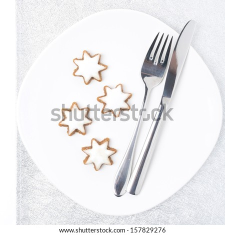 Christmas table setting with cookies on a silver napkin, isolated on white - stock photo