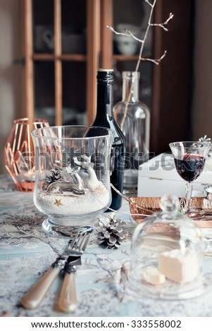 Christmas table setting with decorations and glasses of port wine/sherry and cheese. Retro/classic/imperial style accessories. Natural light photo. Shallow focus. Toned photo.