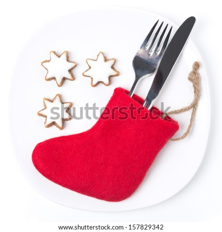 Christmas table setting with red boots and cookies, isolated on white - stock photo