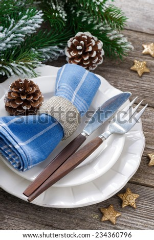 Christmas table setting with spruce branches on a wooden background, close-up - stock photo
