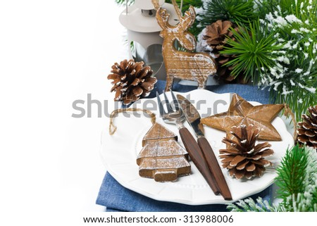 Christmas table setting with wooden decorations and spruce branches over white, selective focus - stock photo
