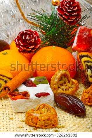 Christmas tangerines, lokum, pinecone and brittle candies on christmas sacking background
