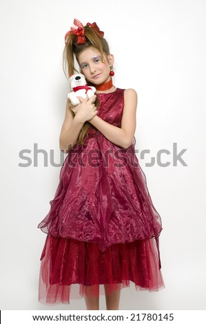 Christmas teenage girl in gorgeous red dress holding a Christmas bear