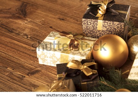 Christmas theme, christmas decoration. presents in boxes on a wooden table with golden baubles, clove, cardamon, star anise, cinnamon. Golden and brownish aesthetics. Place for typography and logo.