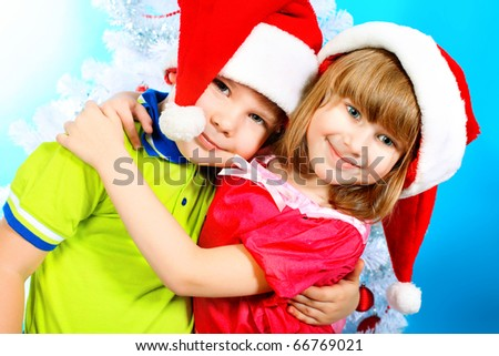 Christmas theme: little boy and girl in santa hats posing together over christmas background.