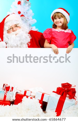 Christmas theme: Santa Claus and little girl holding white board. - stock photo