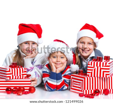 Christmas theme - Smiling happy kids of three in Santa's hat with gift box, isolated on white - stock photo