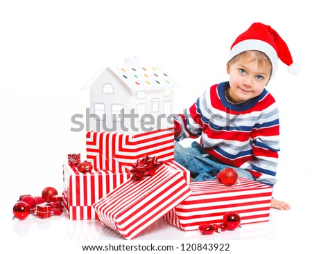 Christmas theme - Smiling little boy in Santa's hat with gift box and gingerbread house, isolated on white - stock photo