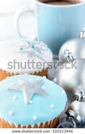 Christmas themed cupcakes in cool, frosty colors with silver ornament baubles and ribbons and a mug of hot cocoa chocolate - stock photo