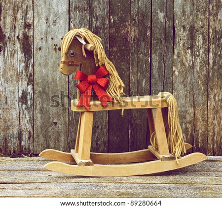 Christmas themed image with an antique rocking horse with a sparkling red Christmas bow around his neck on a rustic wooden backdrop. - stock photo
