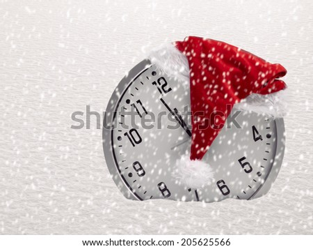 Christmas time concept with clock and santa hat in snow - stock photo