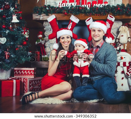 Christmas time. Happy family with baby. Sit near the fireplace - stock photo
