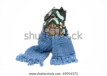 Christmas toy half-timbered house wrapped with scarf -  conceptual view of protecting or isolating house isolated on white background - stock photo