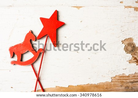 Christmas toy horse and star on a shabby wooden table - stock photo