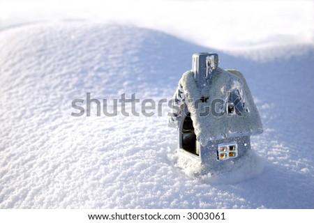Christmas toy house on the snowdrift and sun shadows - stock photo