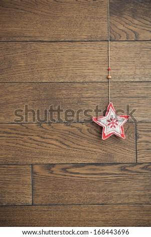 Christmas toy star hanging over wooden background, vertical background