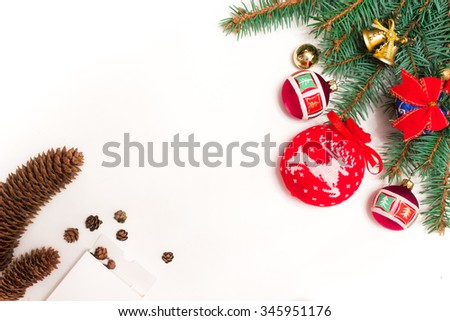 Christmas toys on green fir branch namely big red ball with Christmas reindeer and also red ribbon, garland and bells and fir cones - stock photo