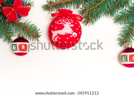 Christmas toys on green fir branch namely big red ball with Christmas reindeer and also red ribbon, garland and bells - stock photo