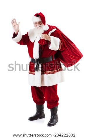 Christmas: Traditional Santa Carrying Bag Of Gifts - stock photo