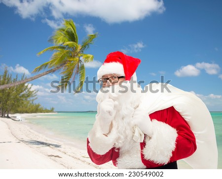 christmas, travel, holidays and people concept - man in costume of santa claus with bag making hush gesture over tropical beach background - stock photo