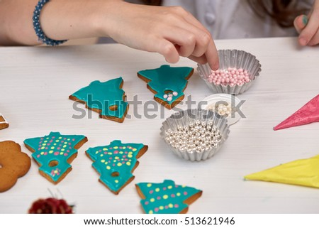 Christmas Treats. Handmade cookies, confection standing on the table. Female hands decorating gingerbreads with sweet icing beads. Christmas and New Year.