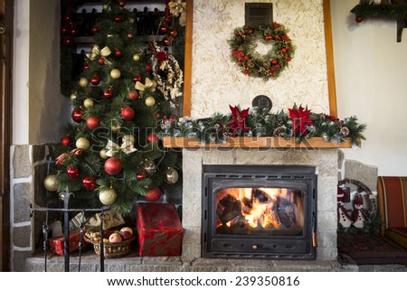 Christmas tree and burning fireplace at home - stock photo