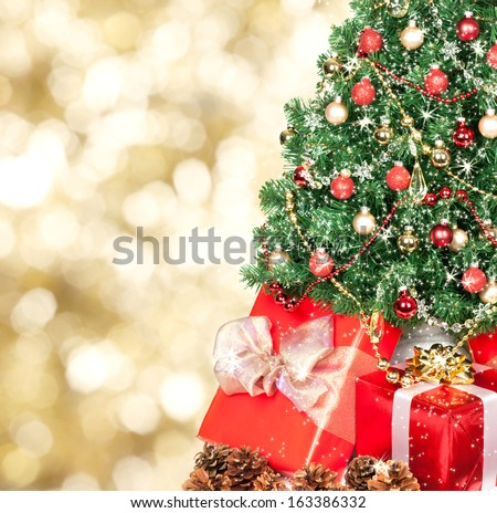 Christmas tree and gifts over golden sparkle background. - stock photo