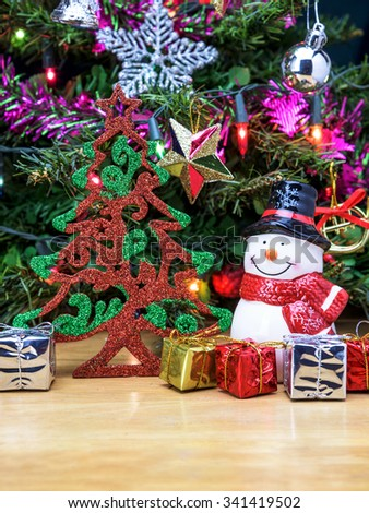 Christmas tree and Snowman ceramic doll with gift box and decorations for background.