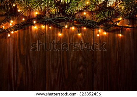 Christmas tree branch and lights on wooden background. View with copy space - stock photo