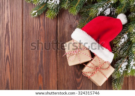 Christmas tree branch and santa hat with gift boxes on wooden table. Top view with copy space - stock photo