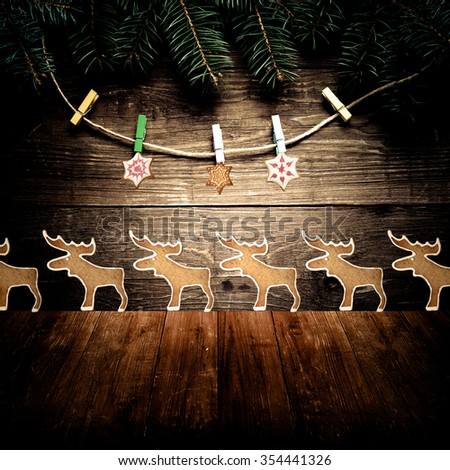 Christmas tree branch, gingerbread homemade cookies with icing and clothespins on rope on a wooden wall over old dark wooden table or board. New year theme. Collage. Space for text. Toned.