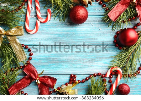 Christmas tree branch with baubles on blue wooden table - stock photo