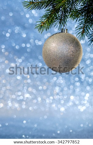 Christmas tree branch with Christmas ball on it over blurred shiny background, close up. Selective focus.