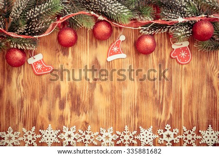 Christmas tree branch with decorations on wood background. Xmas holiday concept - stock photo