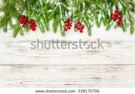 Christmas tree branch with red berries on wooden background. Winter decoration - stock photo