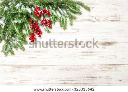 Christmas tree branch with red berries wooden background. Festive decoration. Winter holidays concept - stock photo