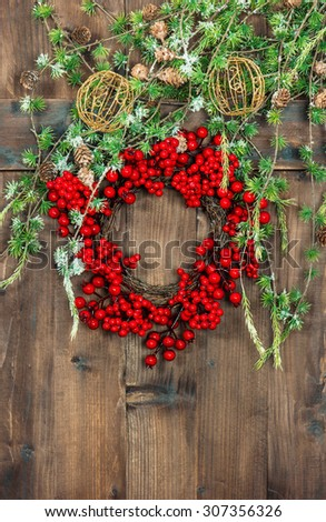 Christmas tree branches and wreath from red berries over rustic wooden background. Festive home interior decoration. Retro style toned picture