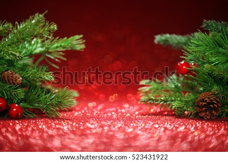 Christmas tree branches on glittering red background