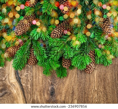 christmas tree branches with cones and colorful lights on wooden background. festive decoration - stock photo