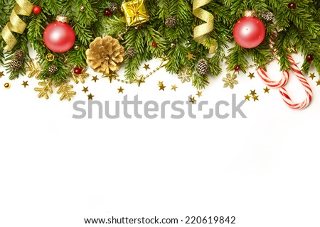 Christmas tree branches with red baubles,  golden stars, snowflakes isolated on white  -  horizontal border - stock photo