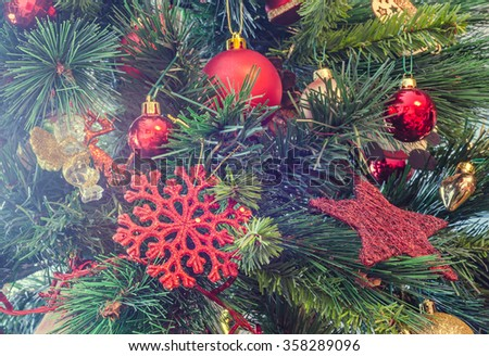 Christmas tree colored ornaments, globe hanging, snow flake, green tree, firs, close up. - stock photo