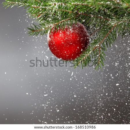 Christmas  tree covered with snow and decorated with red ball  - stock photo