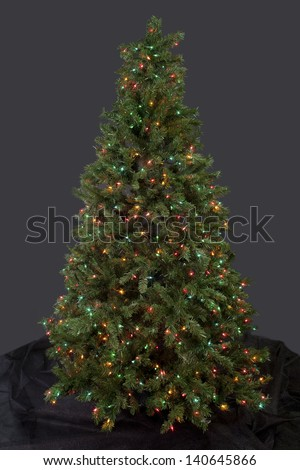 Christmas tree decorated with multi-colored electric lights over dark background. - stock photo