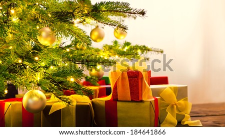Christmas tree decorated with presents in living room - stock photo