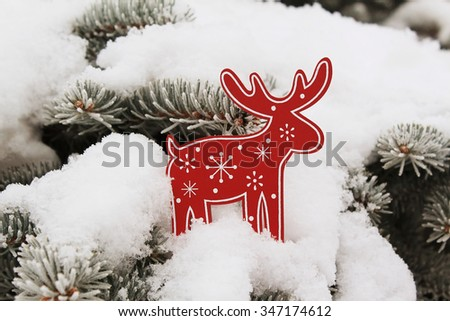 Christmas tree decoration a red deer (elk) on snow on a fir-tree - stock photo