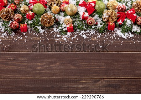 Christmas tree decoration border with gifts, baubles, and pine cones on wood background with copy space - stock photo