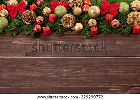 Christmas tree decoration border with gifts, baubles, and pine cones on wood background with copy space